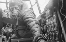 Flying Officer checks settings on control panel on an Avro Lancaster B Mark III